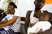 Kouadio Ahou Viviane (right) waits with her 16-month-old boy Emmanuel Ngora Kwame at the NDA health center in Dimbokro, Cote d'Ivoire on Friday June 19, 2009. Emmanuel was suffering from fever, coughing, and a bloated abdomen.