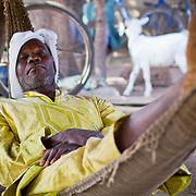 A man enjoys a relaxing stint in a hammock at the butcher's stall, a popular hangout amongst male elders at the Sunday market near Koumbadiouma. Kolda, Senegal.