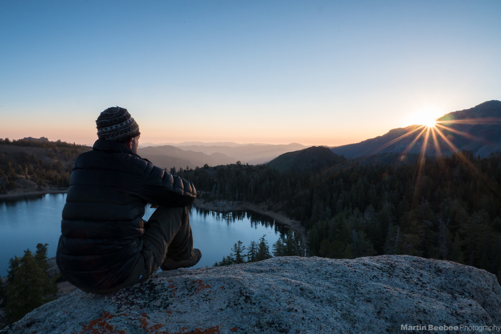 A man watches sunrise over Lower Kinney Lake, Toiyabe National Forest, California