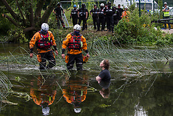 Denham, UK. 24 July, 2020. Police officers from Hampshire Police Marine Support Unit approach a female activist from HS2 Rebellion in the river Colne trying to hinder the destruction of an ancient alder tree in connection with works for the HS2 high-speed rail link in Denham Country Park. A large policing operation involving the Metropolitan Police, Thames Valley Police, City of London Police and Hampshire Police as well as the National Eviction Team was put in place to enable HS2 to remove the tree.