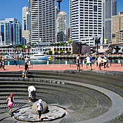 Children playing in the spiral fountain in Darling Harbour on a hot summer's day