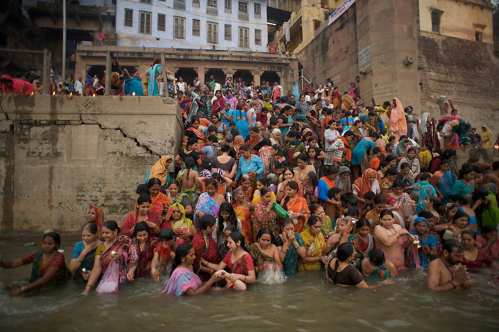 Hindu Pilgrims dip in the Ganges River in Varanasi, India, believing that a dip in the Ganges will cleanse them from their sins.
