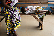 A girl sleeps on a bench as she waits with her mother at the Libreville health center in Man, Cote d'Ivoire on Wednesday July 24, 2013.