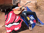 16 OCTOBER 2011 - PHOENIX, AZ: A teenager plays guitar while resting at the Occupy Phoenix protest in downtown Phoenix, AZ, Sunday. About 200 people continued the Occupy Phoenix protest in downtown Phoenix Sunday afternoon. The protest peaked Saturday afternoon at about 2,000 people. Nearly 50 people were arrested late Saturday night on misdemeanor trespassing charges when they tried to camp in a park near downtown and on Sunday the crowd dwindled to 200. Protesters hope to continue the protest through Monday by marching around downtown and picketing banks in the area.   PHOTO BY JACK KURTZ