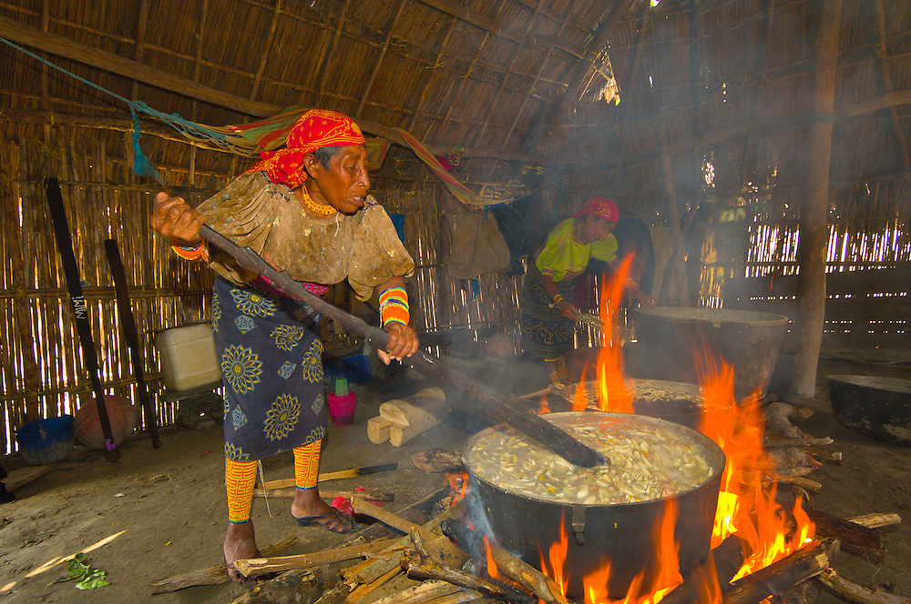 Kuna Indian women wearing native costumes with Mola embroderies cooking in a kitchen in a hut in their village on Corbisky Island, San Blas Islands (Kuna Yala), Caribbean Sea, Panama