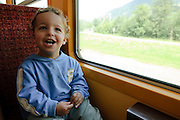 Zillertal, Tyrol, Austria, Steam hauled tourist train on the narrow gauge Zillertalbahn Car interior. Excited boy sits by the window