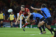 Cory Allen of Wales  gets a pass away as he's tackled by Rodrigo Silva of Uruguay. .Rugby World Cup 2015 pool A match, Wales v Uruguay at the Millennium Stadium in Cardiff, South Wales  on Sunday 20th September 2015.<br /> pic by  Andrew Orchard, Andrew Orchard sports photography.