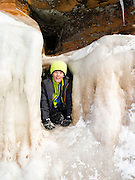 A boy peers out of a small ice cave at the Apostle Island Ice Caves, Makwike Bay, near Bayfield, Wisconsin, on a cold February day.