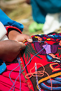 Native Uru woman doing embroidery on the Floating islands of Lake Titicaka, Puno, Peru, South America