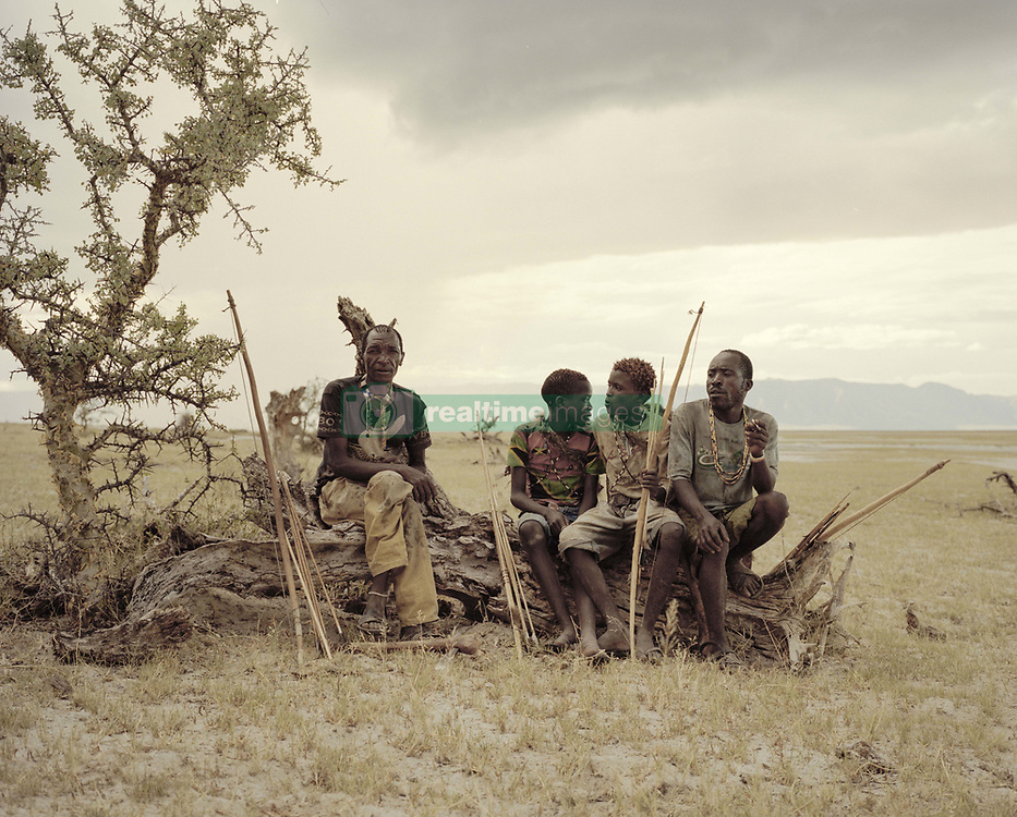 October 3, 2018 - Lake Eyasi, Ngorongoro district, Tanzania - Giaga (50), Manu (14), Osama (15) and Madenye (46) sit and rest on a dead tree.The Hadza are one of the last remaining societies, which remain in the world, that survive purely from hunting and gathering. Very little has changed in the way the Hadza live their lives. But it has become increasingly harder for them to pursue the Hadza way of life. Either the Hadza will find a way to secure their land-rights to have access to unpolluted water springs and wild animals, or the Hadzabe lifestyle will disappear, with the majority of them ending up as poor and uneducated individuals within a Westernized society that is completely foreign to them. The hunter gatherer Hadza way of live is under threat. (Credit Image: © Stefan Kleinowitz/ZUMA Wire)