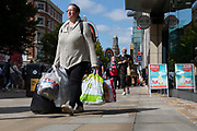 A woman carrying multiple bags of shopping up the citys main commercial street with shoppers wearing face masks in the background on 26th August, 2021 in Manchester, United Kingdom. Many of the UKs high streets and shopping centres are bustling once again, welcoming shoppers back as footfall slowly climbs back to levels seen before the restrictions brought about by the Covid-19 pandemic.