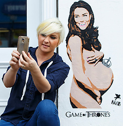 © Licensed to London News Pictures. 13/11/2014. LONDON, UK. A woman takes a picture of herself with a spray-painted picture of the pregnant Duchess of Cambridge, naked with a miniature crown balancing on her belly, made by graffiti artist Pegasus on a wall in Islington, north London. Photo credit : Tolga Akmen/LNP