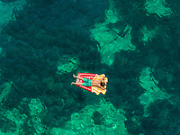 Aerial view of man floating in inflatable on Katomeri beach, Greece.