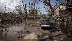 Mud puddles of water and a washed out car litter the front of Hernan Cabrera's house in the Media Luna neighborhood of Toa Baja, Puerto Rico, on October 12, 2017. Photo by Jose A. Iglesias/El Nuevo Herald/TNS/ABACAPRESS.COM