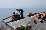 A craftsman and helper lay clay tiles on the roof of a buildingin the town of Monemvassia in the Peloponnese region of the Greek mainland.  Photograph by Dennis Brack