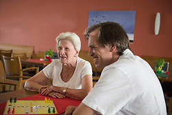 Caretaker with senior woman playing ludo board game at rest home, Bavaria, Germany, Europe