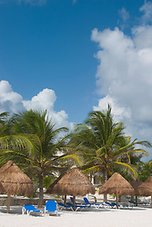"Mexico, Yucatan, Tulum, thatched ""palapa"" umbrellas and lounge chairs on beach with palm trees"