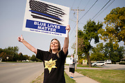 """19 SEPTEMBER 2020 - ALTOONA, IOWA: CONNIE WRIGHT waves at passing motorists during a pro-police rally near the police station in Altoona, a suburb of Des Moines. About 30 people attended an """"Uplifting Our Police"""" rally to show support for not just Altoona police, but law enforcement across the country.      PHOTO BY JACK KURTZ"""