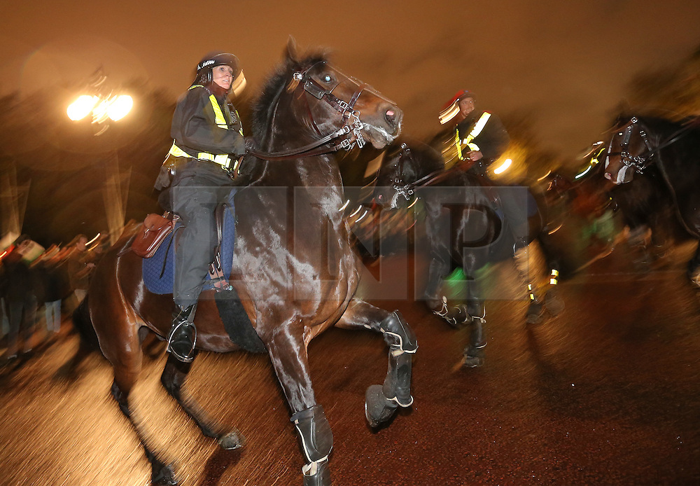 © Licensed to London News Pictures. 05/11/2015. London, UK. Mounted police have trouble controlling their mounts at Buckingham Palace as anti-capitalist protestors launch fireworks during the Million Mask march. Photo credit: Peter Macdiarmid/LNP