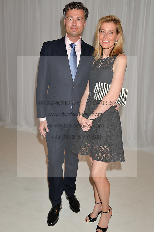LAURENT FENIOU Managing Director of Cartier Ltd and his wife CARINE FENIOU at a dinner hosted by Cartier in celebration of The Chelsea Flower Show held at The Hurlingham Club, London on 19th May 2014.