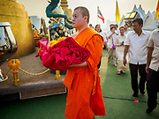 15 NOVEMBER 2018 - BANGKOK, THAILAND:  A monk carries the red cloth that will be used to wrap the chedi at the top of Wat Saket, also called the Golden Mount, during the red cloth ceremony. Wat Saket is on a man-made hill in the historic section of Bangkok. The temple has golden spire that is 260 feet high, which was the highest point in Bangkok for more than 100 years. The temple construction began in the 1800s during the reign of King Rama III and was completed in the reign of King Rama IV. A  red cloth (reminiscent of a monk's robe) is placed around the chedi at the top of  Golden Mount during the weeks leading up to the Thai holy day of Loy Krathong, which is November 22 this year.     PHOTO BY JACK KURTZ