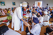 12 AUGUST 2012 - PHOENIX, AZ: Members of the temple hand out prashaad, a sweet pudding made from clarified butter, flour, honey, and water during Sunday services at the Guru Nank Dwara Ashram Sikh temple in central Phoenix. Guru Nank Dwara Ashram is the oldest of three Sikh temples in the Phoenix area. There are about 1,500 Sikh families in the area. Memorials have been held throughout the week to honor the Sikhs killed in the mass shooting in Wisconsin last week. Sunday's service included several mentions of the massacre and was attended by a number of people active in the Phoenix interfaith community.    PHOTO BY JACK KURTZ