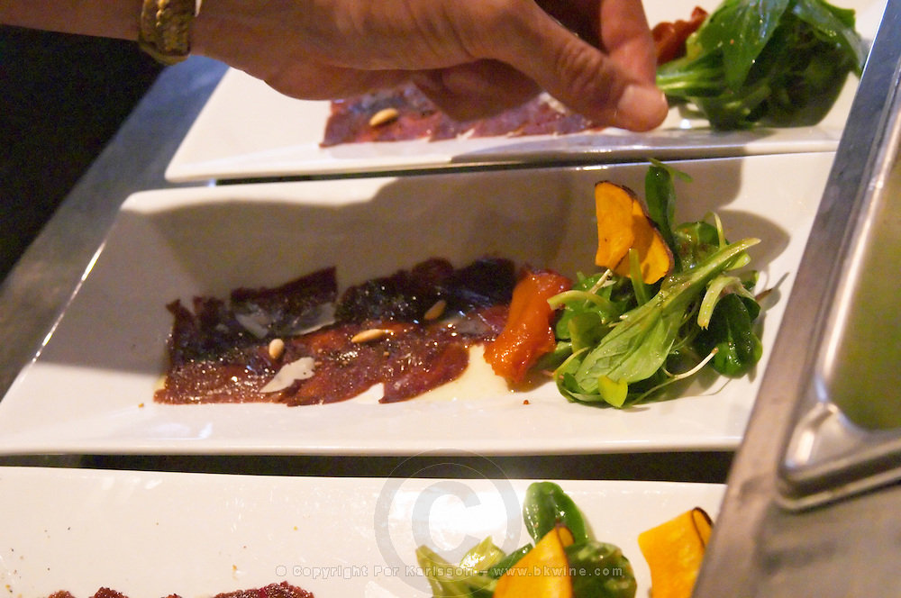 Carpaccio raw marinated beef with pine nuts olive oil balsamic vinegar and mache lettuce, red yellow bell pepper bellpepper fried pumpkin chips on a white plate.. finishing touches done by the chef The O'Farrell Restaurant, Acassuso, Buenos Aires Argentina, South America