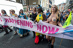 """© Licensed to London News Pictures. 25/08/2021. LONDON, UK.  Climate activists from Extinction Rebellion protest in Soho.  The event is part of the 'Impossible Rebellion' protest to """"target the root cause of the climate and ecological crisis"""" and are ongoing for two weeks until the Government agrees to stop all new fossil fuel investments.  Photo credit: Stephen Chung/LNP"""