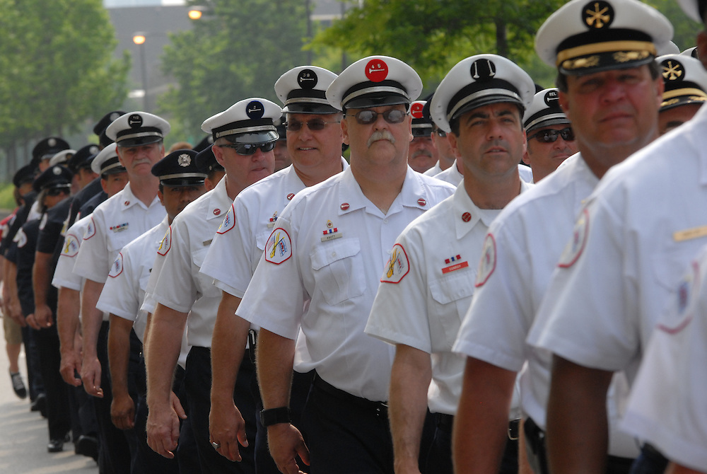 The Chicago Fire Department personnel march in procession on Roosevelt Road, commemorating the services of fallen colleagues before a Memorial Day mass at Holy Family Church.