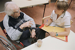 Female occupational therapist making notes while talking to elderly man in a wheelchair; making an assessment on progress,