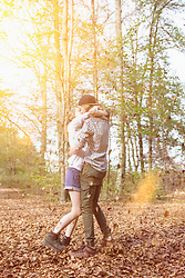 Young couple kissing while autumn leaves falling upon them in a forest, Bavaria, Germany