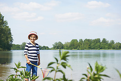 Girl holding a brailer in the lake, Bavaria, Germany