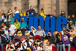 Edinburgh, Scotland, UK. 15 August 2019. Warm sunny weather in Edinburgh brought thousands of tourists onto the Royal Mile to enjoy the many street performers and actors promoting their shows during the Edinburgh Festival Fringe. Pictured. Audience watch a performer in West Parliament Square.  Iain Masterton/Alamy Live News ++ Editorial Use Only ++