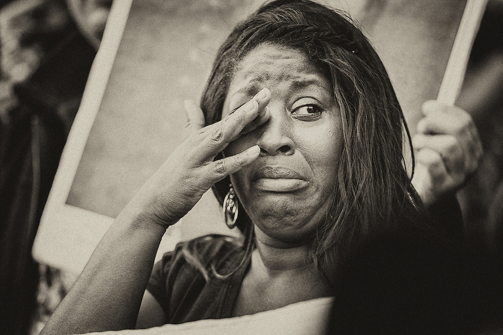 A woman cries as thousands rally for a protest in Oakland.