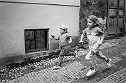 Two boys running down a street in Zizkov.