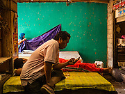 10 OCTOBER 2016 - UBUD, BALI, INDONESIA:  A man checks his smart phone in the basement of the market in Ubud. The morning market in Ubud is for produce and meat and serves local people from about 4:30 AM until about 7:30 AM. As the morning progresses the local vendors pack up and leave and vendors selling tourist curios move in. By about 8:30 AM the market is mostly a tourist market selling curios to tourists. Ubud is Bali's art and cultural center.     PHOTO BY JACK KURTZ