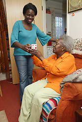 Daughter giving mother a cup of tea.