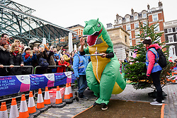 © Licensed to London News Pictures. 08/12/2018. LONDON, UK.  A competitor dressed as a dinosaur takes part in The 38th Great Christmas Pudding Race in Covent Garden, raising funds for Cancer Research as well as having a lot of festive fun.  Photo credit: Stephen Chung/LNP
