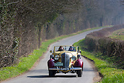 Old classic 1936 Buick 40C open top vintageant convertible car driving through country lanes in the Cotswolds, Oxfordshire, UK