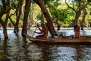 A father and daugther paddle through the flooded forest south of Kampong Phluk, Cambodia.