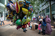 Muslim family pass helium filled balloon seller in Birmingham, United Kingdom. These balloons, all being held in a large bunch depict all sorts of characters from cartoons and tv.