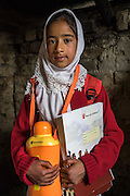 Hafiza, 10, holds items from the education kit in her collapsed house in Purnishadashah village, Jammu and Kashmir, India, on 24th March 2015. Hafiza's house was destroyed in the floods forcing her family to move in with relatives. Save the Children supported the family with kitchen items, hygiene kits, food baskets, blankets, a solar powered lamp and education kits for the children. Photo by Suzanne Lee for Save the Children