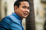 09 SEPTEMBER 2014 - BANGKOK, THAILAND:  Thai Prime Minister GENERAL PRAYUTH CHAN-OCHA walks back to his office after praying at a Buddhist shrine on the grounds of Government House in Bangkok. Thai Prime Minister General Prayuth Chan-ocha named a cabinet that was dominated by members of the security forces to govern Thailand through at least a year of political reforms before elections are held. Prayuth and the cabinet met for the first time Tuesday. Before the meeting Prayuth said a prayer at a Buddhist shrine on the grounds of Government House, which is the Prime Minister's office. Prayuth seized power in a military coup in May. He was unanimously selected as Prime Minister by the National Legislative Assembly (NLA), the acting parliamentary body. Prayuth and his aides personally selected the members of the NLA after they seized power.      PHOTO BY JACK KURTZ