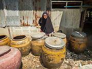 14 JULY 2015 - THAILAND:   A homeowner in Nakhon Nayok province opens her water storage jars so provincial workers can give her water.. The drought that has crippled agriculture in central Thailand is now impacting residential areas near Bangkok. The Thai government is reporting that more than 250,000 homes in the provinces surrounding Bangkok have had their domestic water cut because the canals that supply water to local treatment plants were too low to feed the plants. Local government agencies and the Thai army are trucking water to impacted communities and homes. Roads in the area have started collapsing because of subsidence caused by the retreating waters. Central Thailand is contending with drought. By one estimate, about 80 percent of Thailand's agricultural land is in drought like conditions and farmers have been told to stop planting new acreage of rice, the area's principal cash crop.      PHOTO BY JACK KURTZ