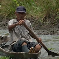 A Yanayacu Indian fisherman paddles his canoe in the Yanayacu River in Peru's Amazon Jungle.