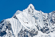 The sharp peak of Gandharba Chuli (20,500 feet / 6248 meters), with fluted ice ridges, in the Annapurna Range of Nepal, seen from the Annapurna Sanctuary.