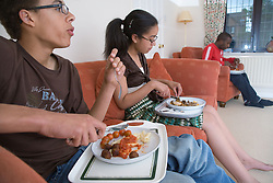 Family watching television and eating dinner,