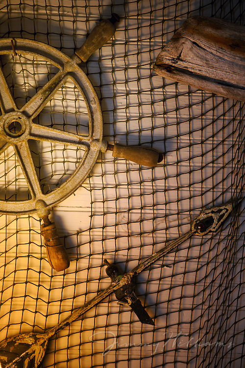 A captains wheel, weather vane, and driftwood are displayed on old fishing net to create a unique work of art inside an old coastal cottage in Nags Head, North Carolina