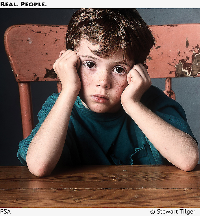 Portrait of a sad boy leaning his elbows on a wooden table.