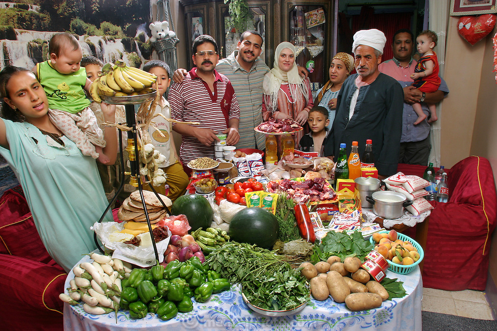 (MODEL RELEASED IMAGE). The Ahmeds' extended family in the Cairo apartment of Mamdouh Ahmed, 35 (glasses), and Nadia Mohamed Ahmed, 36 (brown headscarf), with a week's worth of food. Hungry Planet: What the World Eats (p. 118).